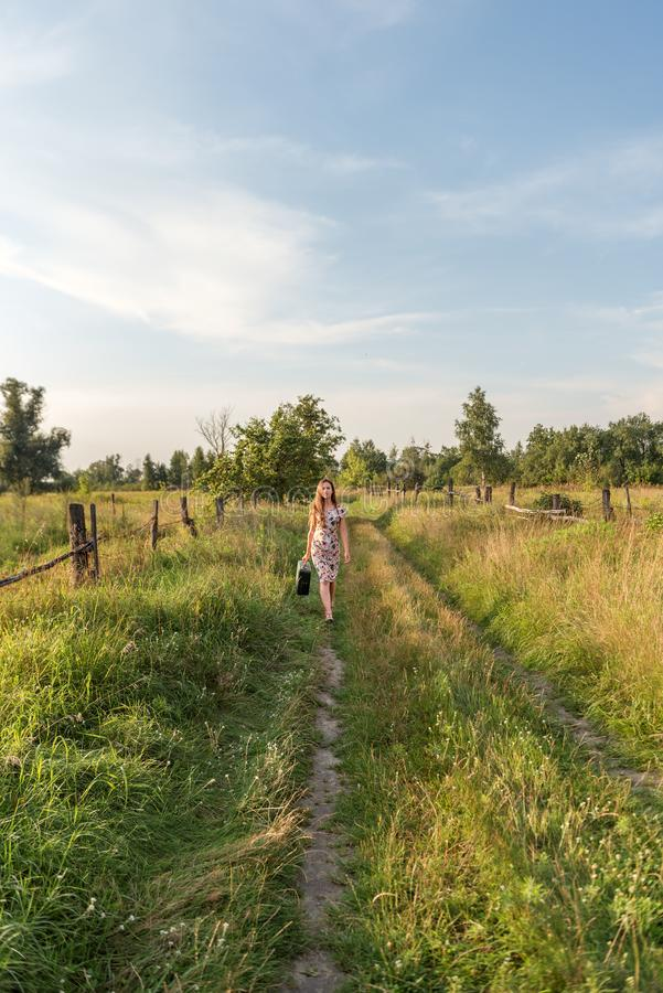 一件淡粉红的礼服的一个少妇带着葡萄酒手提箱沿乡下公路走长满与在村庄围场a之间的草 免版税图库摄影