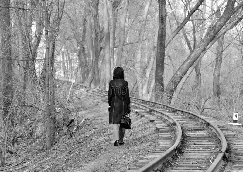 一件温暖的外套的一个女孩沿铁轨,黑白照片走 免版税库存照片
