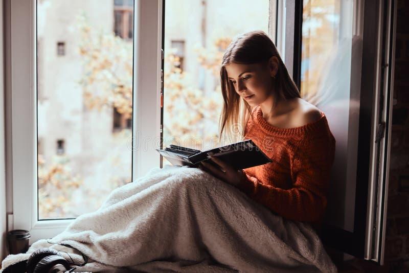 一件温暖的毛线衣的年轻女人用毯子报道了她的腿,看相册,坐窗台 库存图片