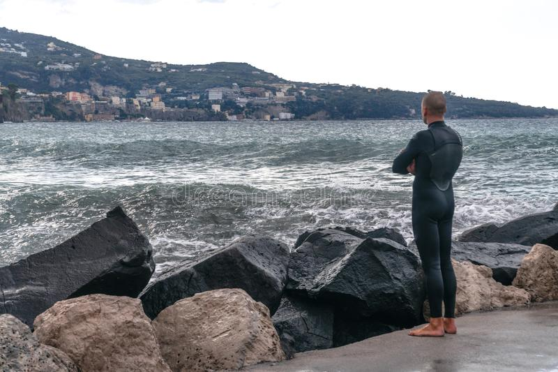 一件潜水衣的人,冲浪者,站立在岸和在山的背景中看波浪,索伦托意大利 库存照片