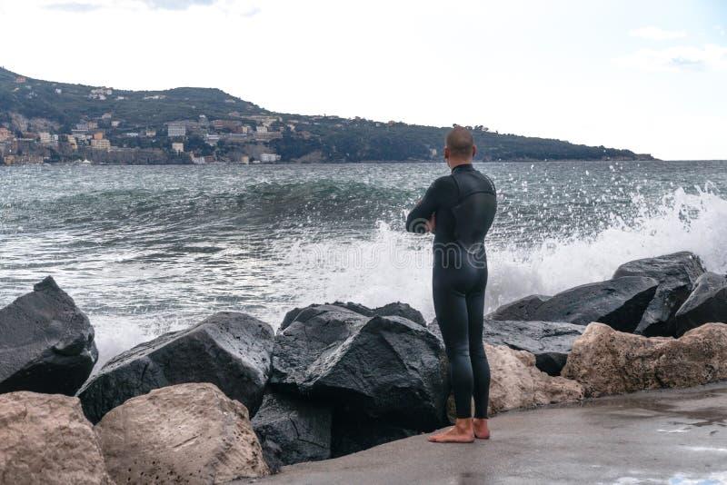 一件潜水衣的人,冲浪者,站立在岸和在山的背景中看波浪,索伦托意大利 免版税库存照片