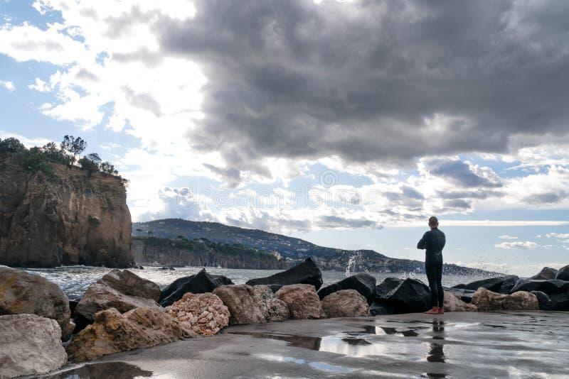一件潜水衣的人,冲浪者,站立在岸和在山的背景中看波浪,索伦托意大利 图库摄影