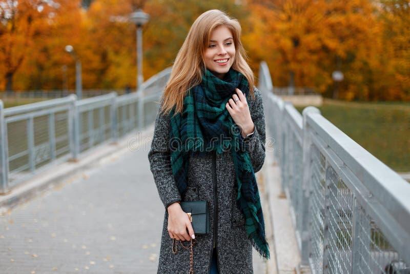 一件灰色典雅的时髦的外套的逗人喜爱的微笑的年轻女人在一条绿色葡萄酒方格的围巾 库存图片