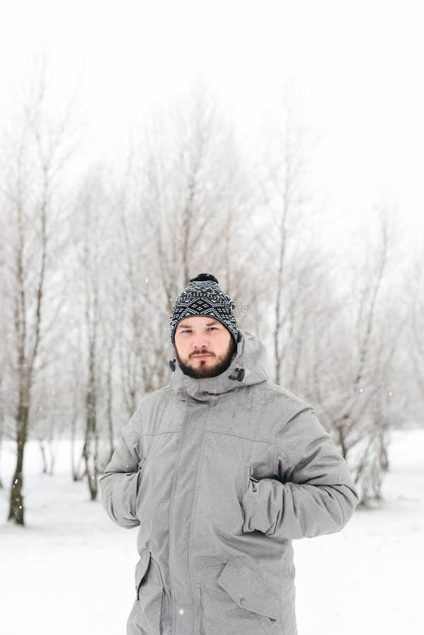 一件灰色夹克的一个人在冬天森林里 免版税库存照片