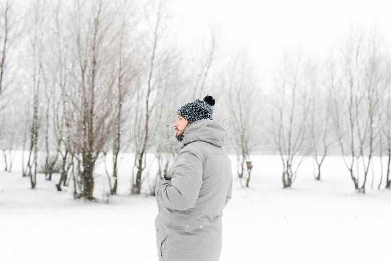 一件灰色夹克的一个人在冬天森林里 图库摄影