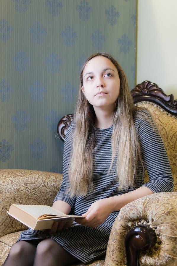 一件灰色礼服梦想的女孩与在椅子的一本书 库存图片