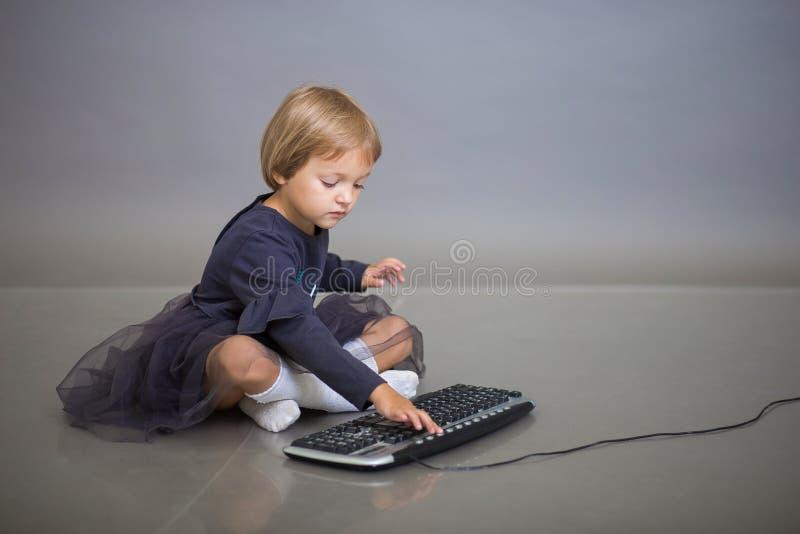 一件灰色礼服的女孩坐灰色背景和戏剧与键盘从计算机 图库摄影