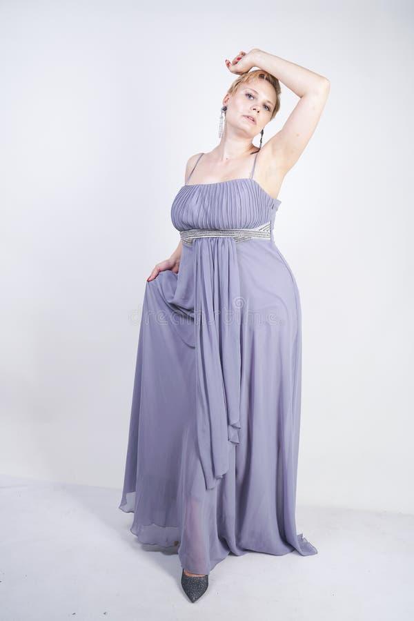 一件灰色长的礼服的典雅的厚实的女性 晚礼服身分的俏丽的正大小妇女在白色演播室背景 ?? 免版税库存照片