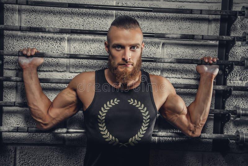 一件灰色T恤杉的有胡子的肌肉人 免版税库存图片