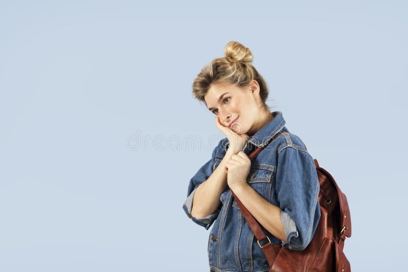一件牛仔布夹克的美丽的学生女孩有在她的肩膀的一个背包的在蓝色背景的演播室 概念  免版税库存图片