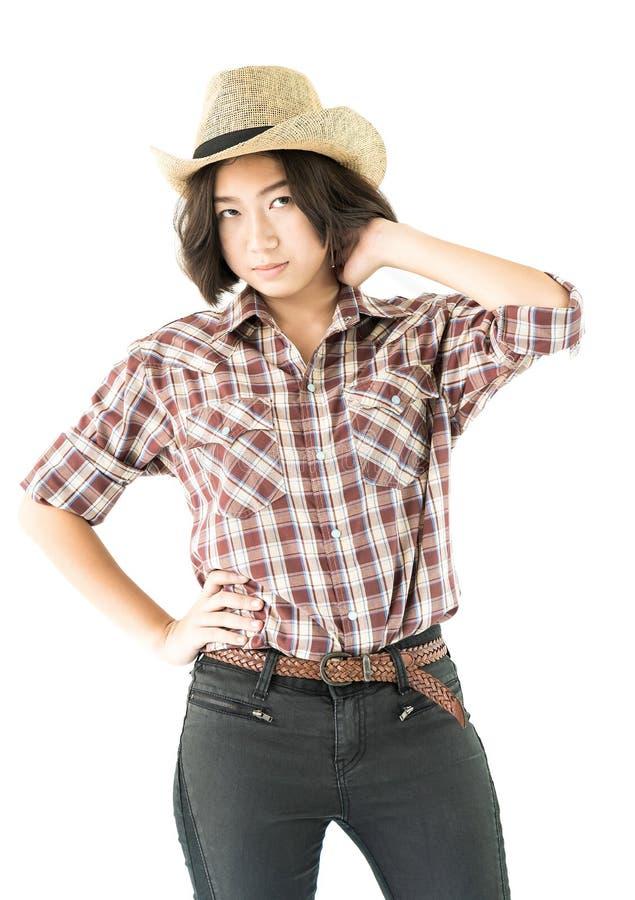 一件牛仔帽和格子花呢上衣的少妇用在她的帽子的手 库存照片