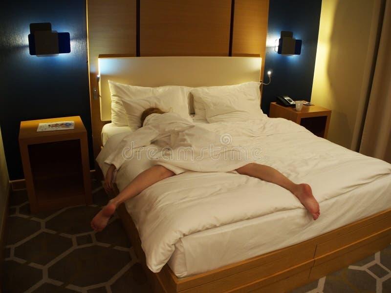 一件白色外套的一个女孩在她的胃的一张大床上说谎在诺富特旅馆里 俄罗斯索契05 10 2019? 免版税库存照片