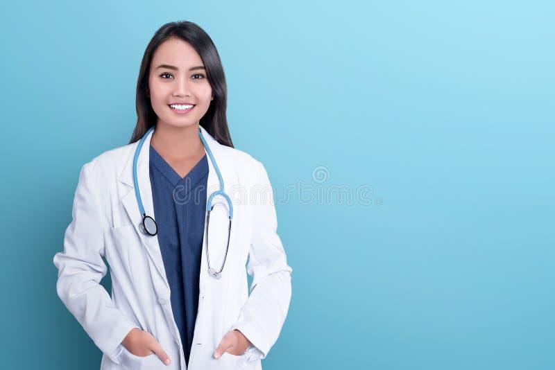 一件白色外套的微笑的亚裔妇女医师 库存图片