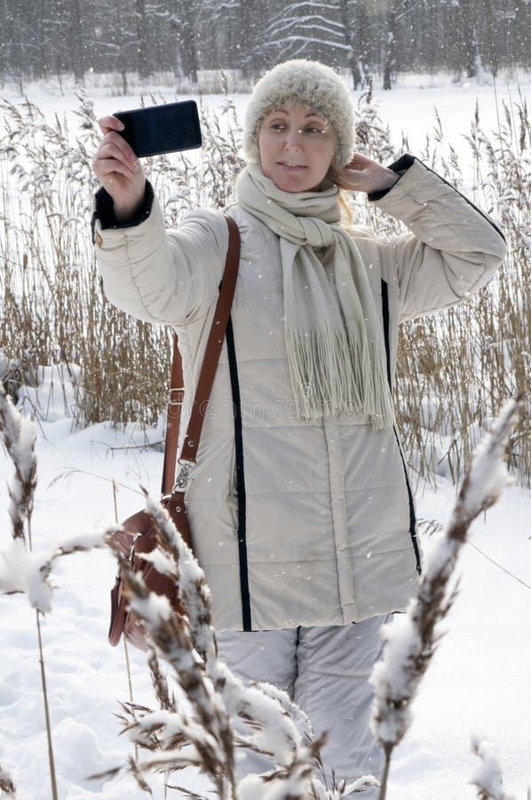 一件白色夹克的年轻女人在冬天森林湖的海岸做一selfie 免版税库存照片