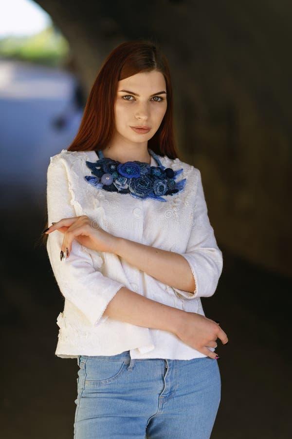 一件白色夹克的时髦的美丽的女孩 免版税库存照片