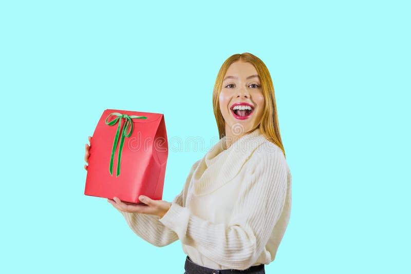 一件白色女衬衫的一个美丽的甜红发女孩拿着一个礼物袋子一个箱子与一绿色天鹅绒丝带上升的红色 免版税库存图片
