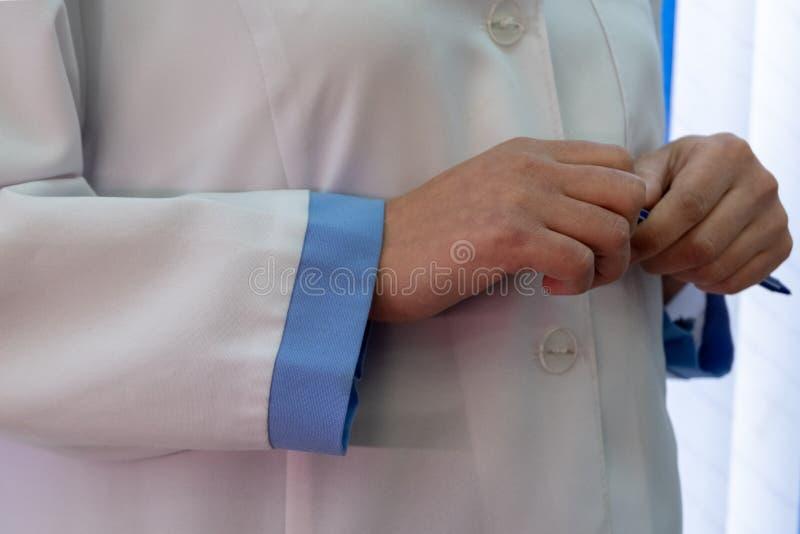 一件白色实验室外套的一名妇女有蓝色袖口的 有平底锅的女性医生手 特写镜头 图库摄影