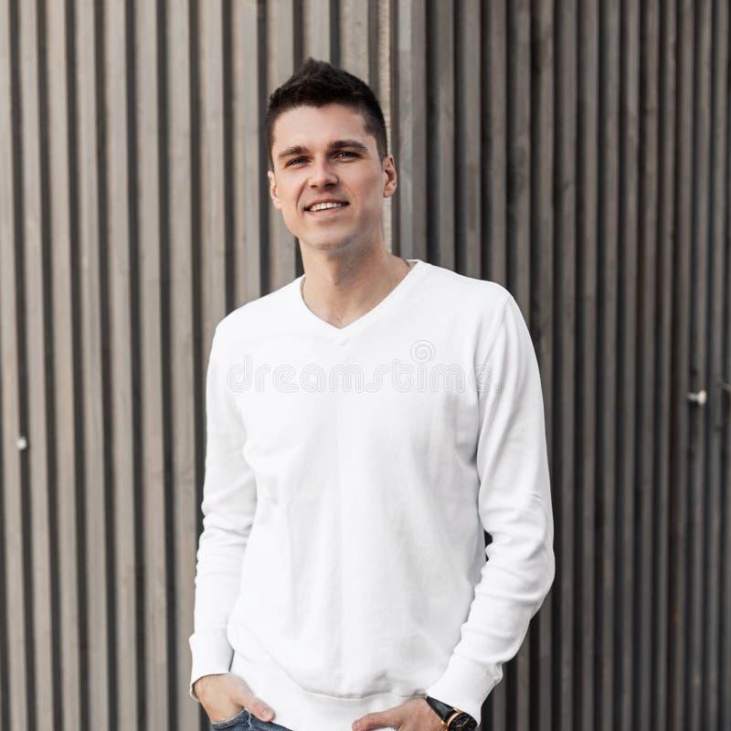 一件白色时髦的衬衣的可爱的快乐的年轻人有逗人喜爱的微笑的在条纹的一个木葡萄酒大厦附近站立 免版税库存图片
