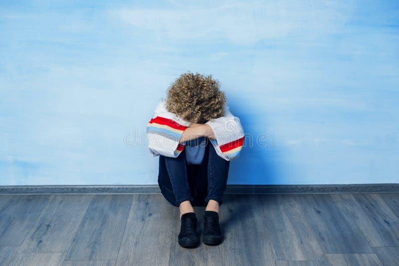 一件白色毛线衣的一个沮丧的年轻人有彩虹样式的坐倾斜对蓝色墙壁,拥抱膝盖, 免版税库存照片
