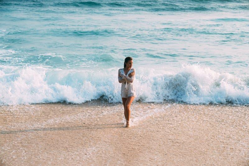 一件白色海滩礼服的一个美丽的性感的亭亭玉立,被晒黑的女孩站立湿在海滩,衬托 库存照片