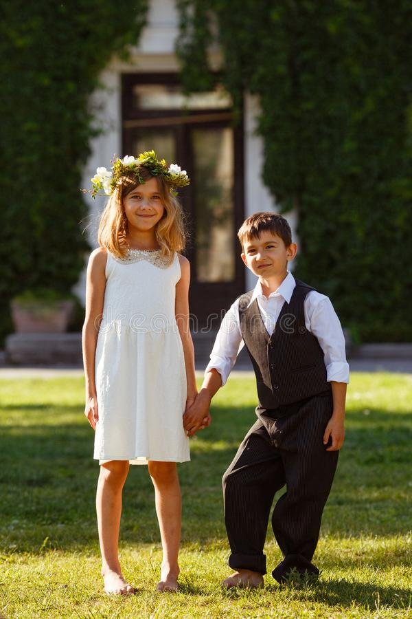 一件白色礼服的一个女孩握在一套时兴的衣服的一只男孩` s手 库存图片