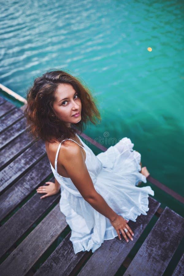 一件白色礼服的一美女坐木地板在蓝色湖附近和神色对照相机 库存照片