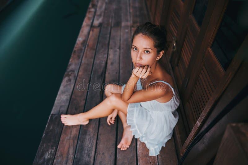 一件白色礼服的一美女坐木地板在蓝色湖附近和神色对照相机 免版税库存照片