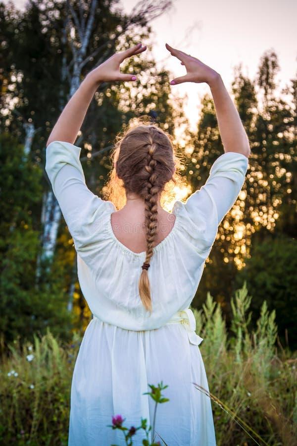 一件白色礼服的女孩看日落在森林里呼吸并且放松 有辫子发型的妇女考虑自然的 免版税图库摄影