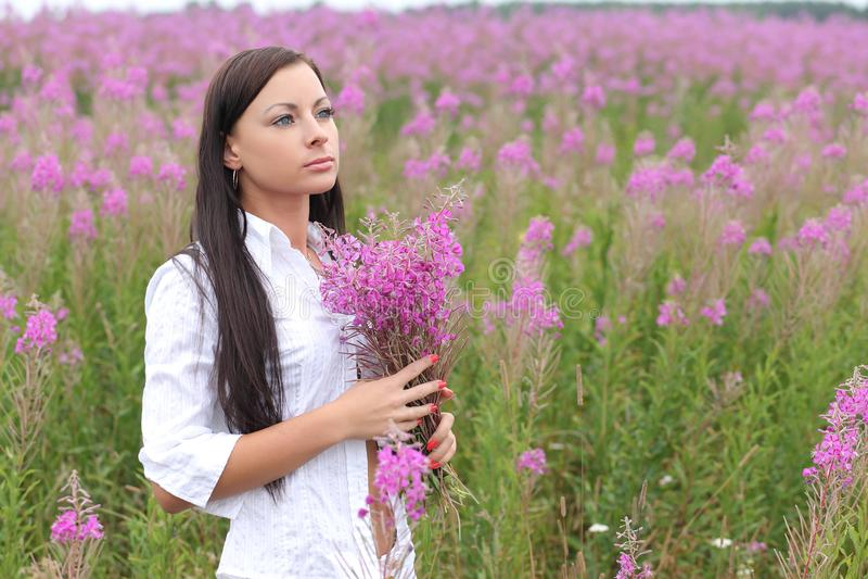 一件白色礼服的妇女在高草背景  免版税库存图片