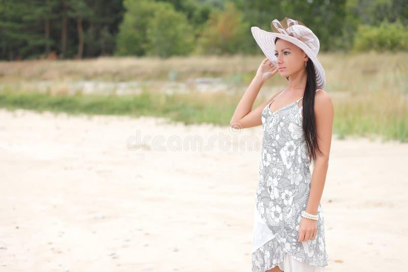 一件白色礼服的妇女在高草背景  库存图片