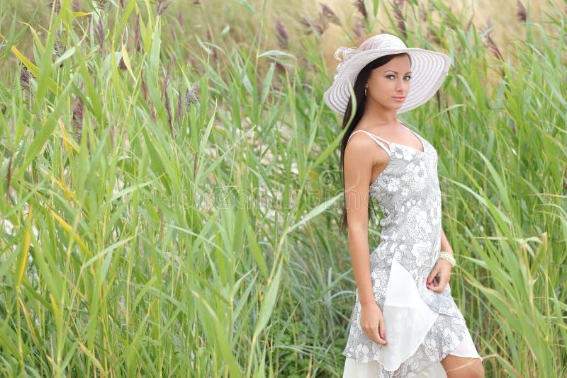一件白色礼服的妇女在高草背景  免版税库存照片