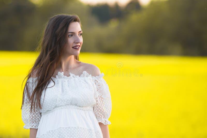 一件白色礼服的怀孕的女孩 美丽的孕妇室外自然画象白色礼服的 库存照片