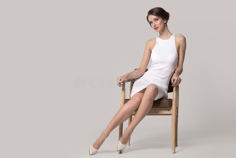 一件白色礼服的时髦的女人坐椅子 库存图片