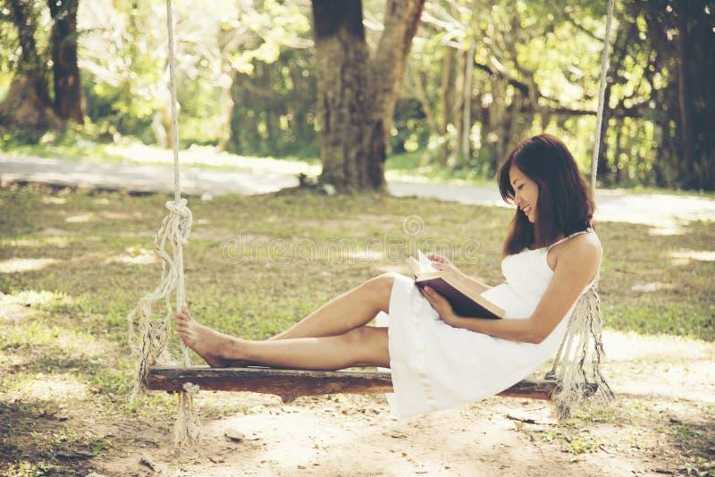 一件白色礼服的美丽的亚裔妇女坐木摇摆 库存图片