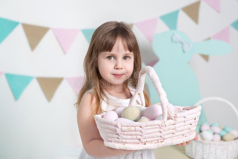 一件白色礼服的美丽的女孩站立与复活节篮子 许多不同的五颜六色的复活节彩蛋,五颜六色的内部 免版税库存照片
