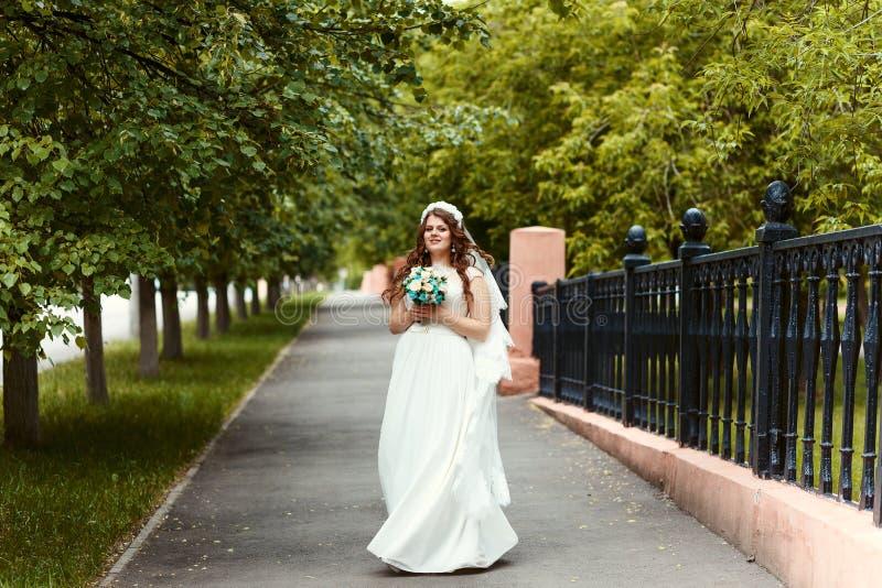 一件白色礼服的美丽的快乐的与花束的新娘和面纱在她的看照相机的手上在公园在全长su 免版税库存照片
