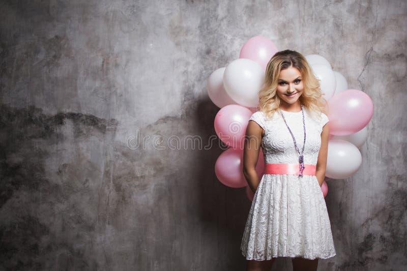一件白色礼服的迷人的年轻金发碧眼的女人有桃红色balloonsbehind的后面 有气球的愉快和快乐的女孩 库存图片