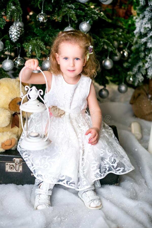 一件白色礼服的逗人喜爱的小女孩在圣诞树附近坐手提箱,拿着有一个蜡烛的一个手电在她的手上 库存图片