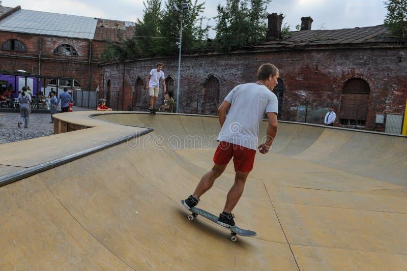 一件白色简单的T恤杉的一个年轻人没有在红色短裤的图画在冰鞋训练场 免版税图库摄影