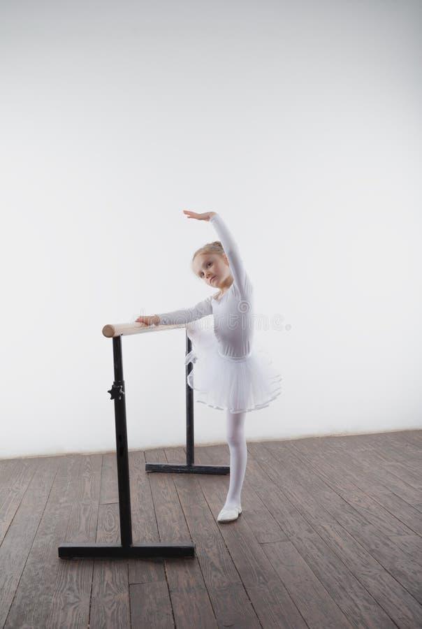 一件白色芭蕾舞短裙的年轻芭蕾舞女演员女孩 跳舞古典芭蕾的可爱的孩子在有木地板的一个白色演播室 儿童舞蹈 库存照片