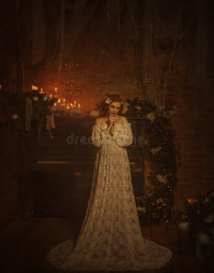 一件白色葡萄酒礼服的一个女孩有开放肩膀的站立以一架老钢琴和蜡烛为背景 哥特式 免版税图库摄影