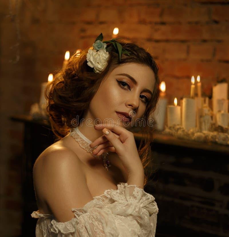 一件白色葡萄酒礼服的一个女孩有开放肩膀的站立以一架老钢琴和蜡烛为背景 哥特式 免版税库存图片