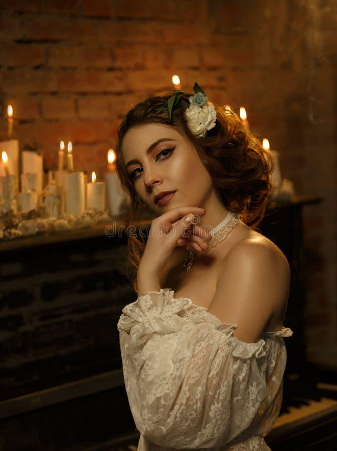 一件白色葡萄酒礼服的一个女孩有开放肩膀的站立以一架老钢琴和蜡烛为背景 哥特式 库存照片