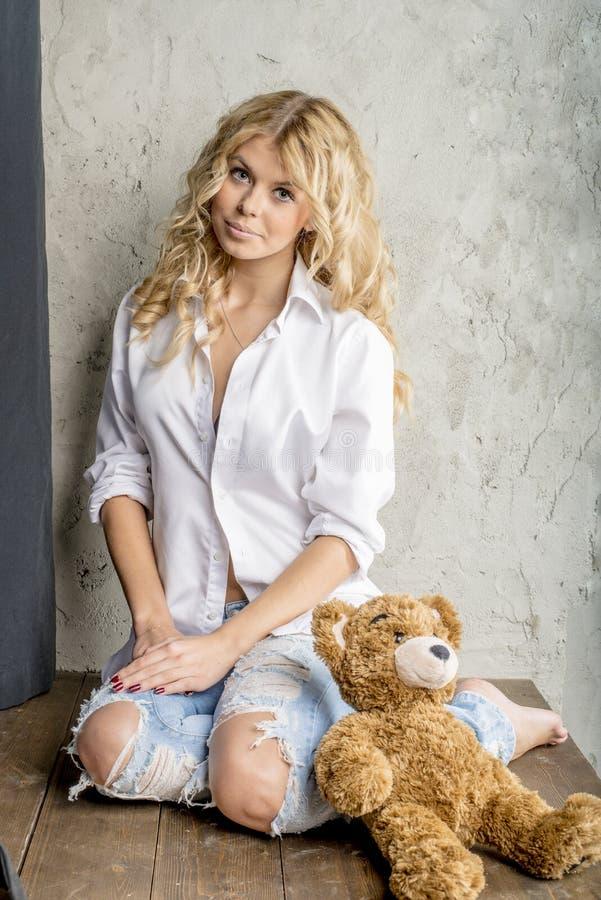 一件白色衬衣和牛仔裤的年轻美丽的女孩金发碧眼的女人有空白的 图库摄影
