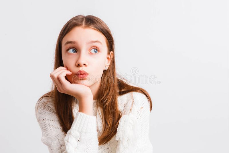 一件白色被编织的毛线衣的情感青少年的女孩在浅灰色的背景 文本的空间 免版税图库摄影