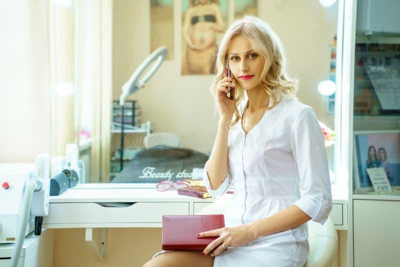 一件白色长袍的一年轻女人拜访电话的在美容师办公室 图库摄影