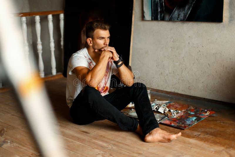 一件白色T恤杉的年轻英俊的创造性的人在艺术坐 图库摄影