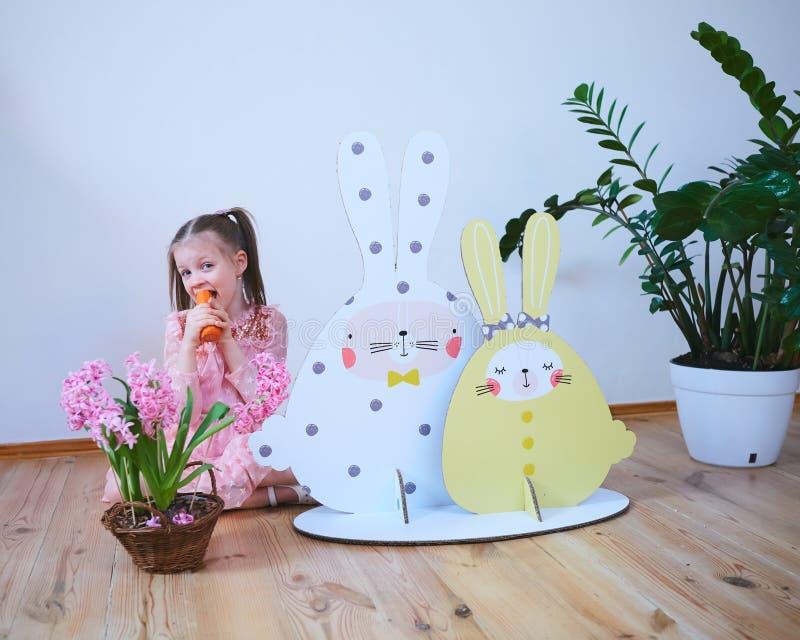 一件礼服的复活节2019美丽的女孩有复活节装饰的 大复活节兔子 很多不同五颜六色 库存照片