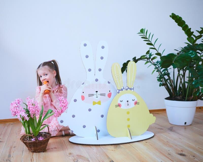 一件礼服的复活节2019美丽的女孩有复活节装饰的 大复活节兔子 很多不同五颜六色 图库摄影