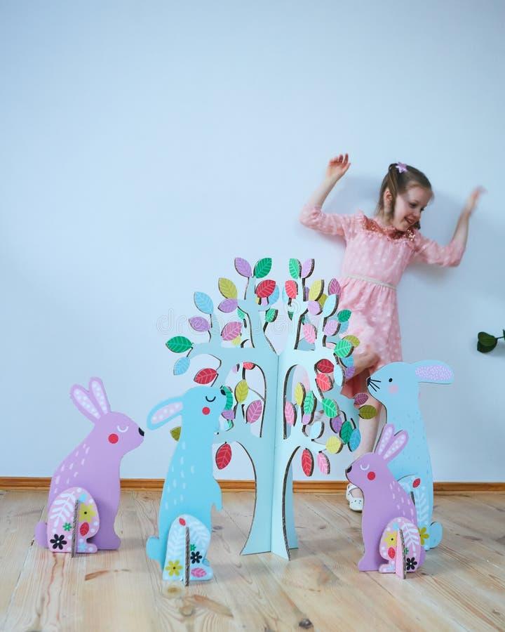 一件礼服的复活节2019美丽的女孩有复活节装饰的 大复活节兔子 很多不同五颜六色 免版税库存图片
